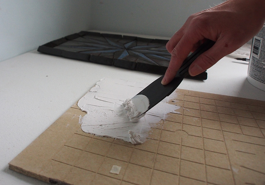 applying tile adhesive with a small spatula